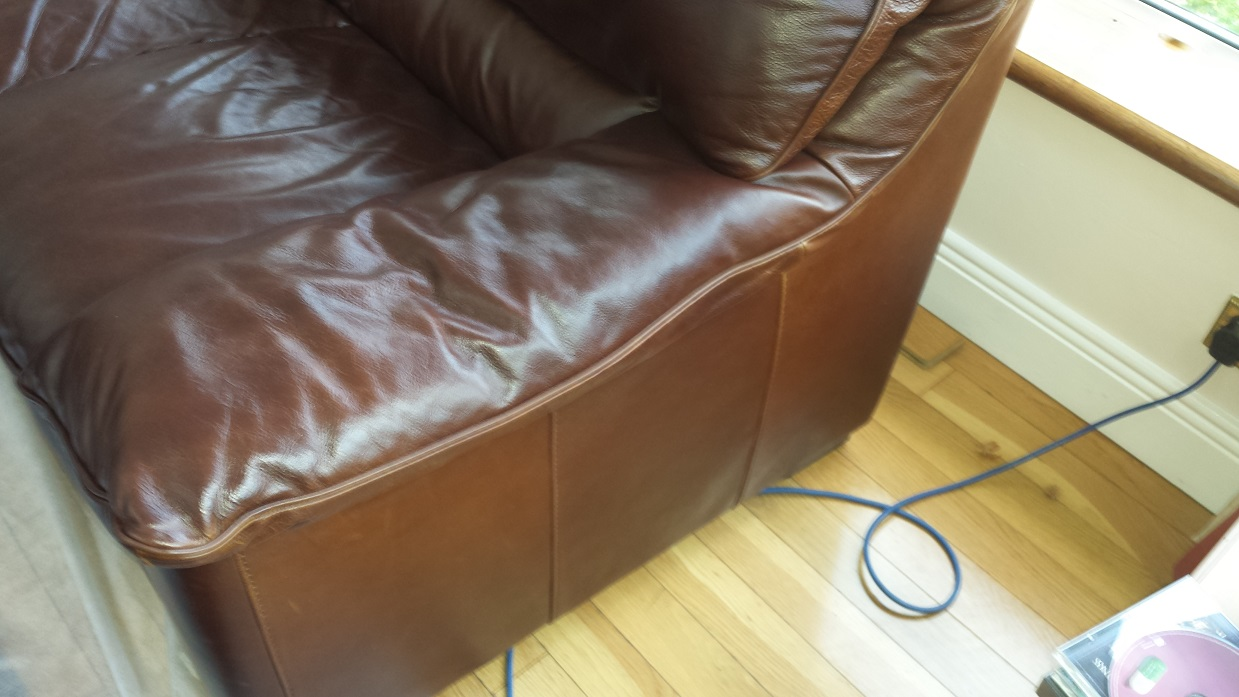 Brown leather sofa arm with colour fading back to like new